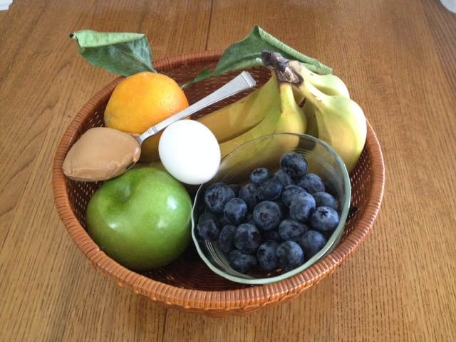 Basket filled with with fruits, a spoon of peanut butter, and a hard boiled egg
